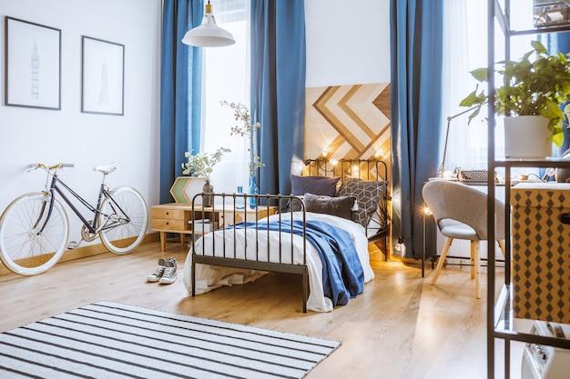 Niebieskie zasłony i rower w przytulnym wnętrzu sypialni z roślinami na szafce obok łóżka ze światłami