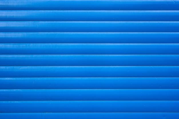 Niebieskie żelazo blaszane ogrodzenie pokryte tłem. metalowa tekstura