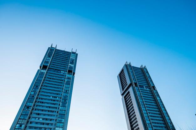 Niebieskie, zimne odcienie kolorów drapaczy chmur ze światłem słonecznym - perspektywa patrzenia w górę, widok na miasto biur i dzielnicy finansowej z pracownikami banków i ubezpieczeń w pracy