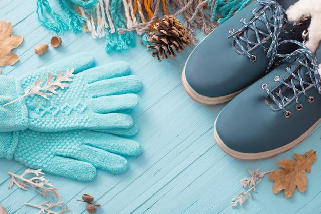 Niebieskie zimowe buty i rękawiczki na niebieskim drewnianym