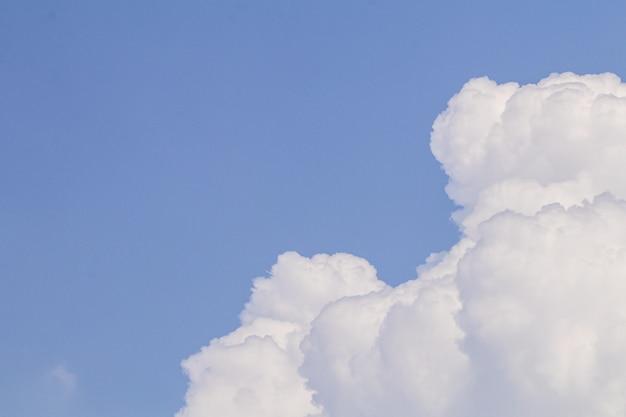 Niebieskiego nieba i bielu obłoczny tło.