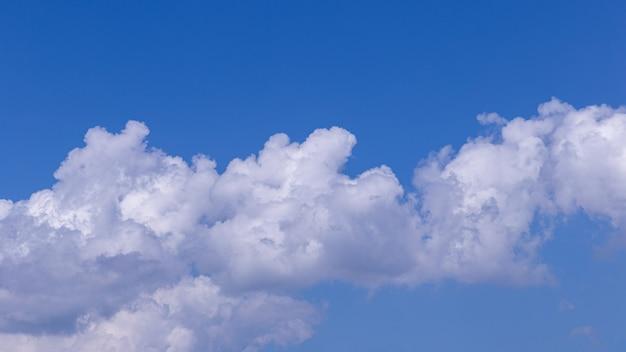 Niebieskiego nieba tło z bielem chmurnieje na słonecznym dniu