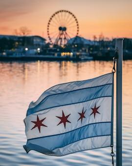 Niebiesko-biała flaga z gwiazdami z diabelskim młynem i budynkami za jeziorem w tle