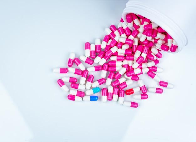 Niebiesko-biała kapsułka zanieczyszczona różowo-białymi kapsułkami. tabletki kapsułki rozłożone z plastikowej butelki leku. przemysł farmaceutyczny. zażywanie antybiotyków w szpitalach.