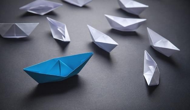 Niebiesko-biała łódź papierowa. koncepcja przywództwa