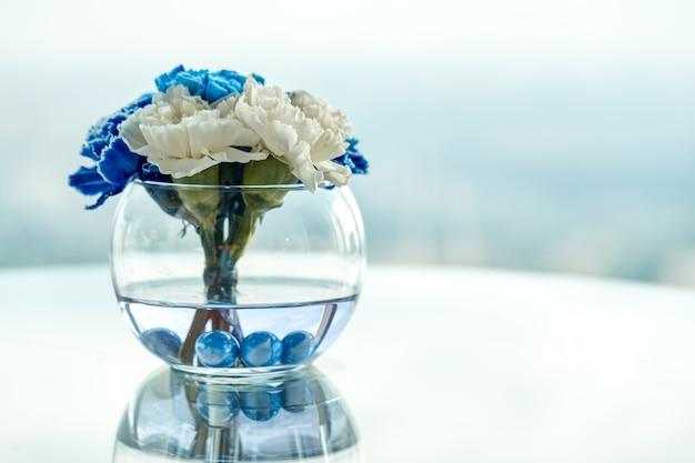 Niebiesko-białe orchidee w wazonie na stole, piękny układ kwiatów w biurze.