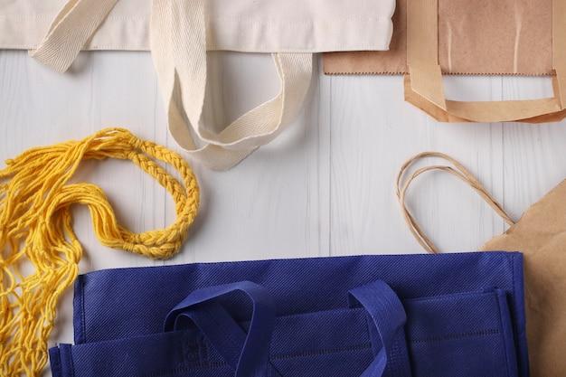 Niebiesko-białe torby na zakupy, żółta torba z siatki i papierowe torby na produkty na białym tle, koncepcja zero waste, widok z góry