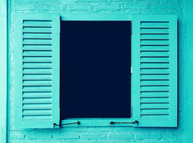 Niebiesko-kolorowe drewniane okno z okiennicami na mur z cegły