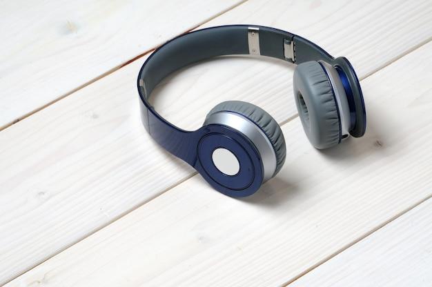 Niebiesko-srebrne, nowoczesne słuchawki do słuchania muzyki na białym drewnie