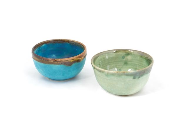 Niebiesko-zielone ręcznie robione gliniane miski na białym tle