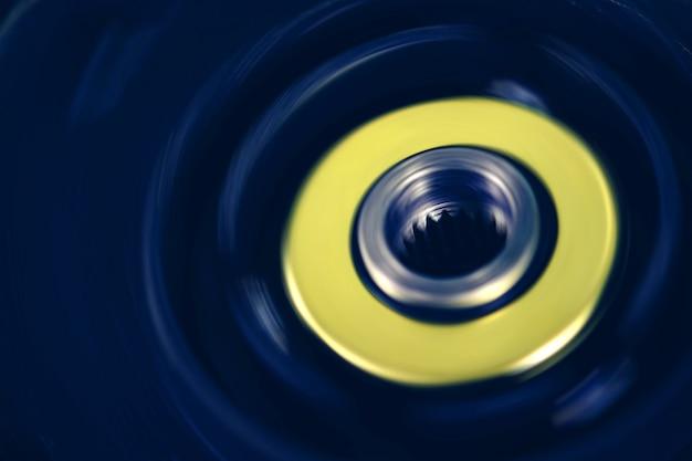 Niebiesko-żółte urządzenie wykonane z tworzywa sztucznego z obracaną metalową zębatką. żywy mechanizm grunge z miejsca na kopię. tło z urządzenia retro z bliska.
