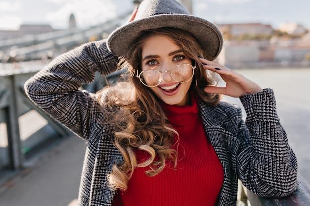 Niebieskooka brunetka kobieta z wyrazem twarzy szczęśliwy pozuje z przyjemnością na rozmycie tła miasta w jesienny dzień