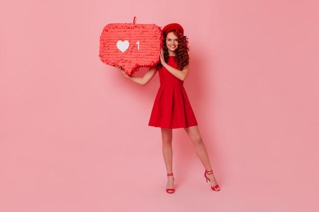 Niebieskooka dama w świetnym nastroju zachowuje ogromne lajki. dziewczyna w berecie i czerwonej sukience jest urocza uśmiechnięta na różowej przestrzeni.