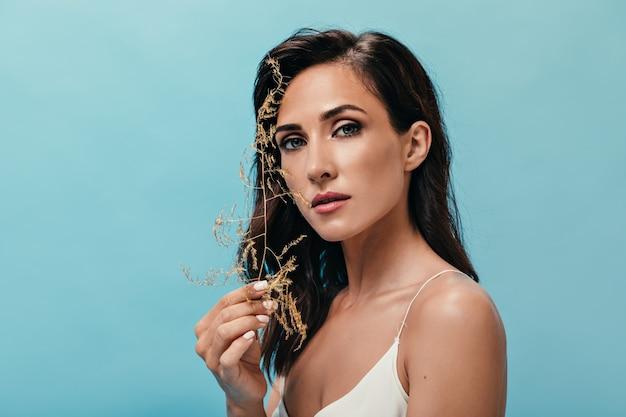 Niebieskooka dziewczyna patrzy w kamerę i trzyma suszoną trawę. brunetka z krótkimi falującymi włosami z białym manicure pozuje na na białym tle.