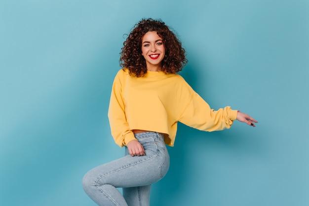 Niebieskooka dziewczyna z jasnymi ustami i śnieżnobiałym uśmiechem pozuje na niebieskiej przestrzeni. dama w żółtym swetrze i obcisłych dżinsach tańczy.