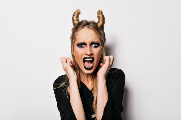 Niebieskooka europejka pozuje w kostiumie wiedźmy z niezadowolonym wyrazem twarzy. zły wampir blondynka z czarnym makijażem.