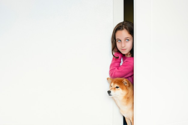 Niebieskooka kaukaska dziewczynka z psem shiba inu wystającym z drzwi sypialni: