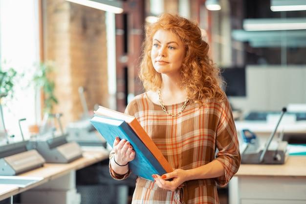 Niebieskooka kobieta. niebieskooka kędzierzawa kobieta w stylowym naszyjniku stojąca w biurze trzymająca książki