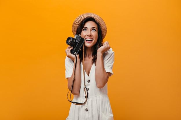 Niebieskooka kobieta w kapeluszu trzymając aparat i raduje się na pomarańczowym tle