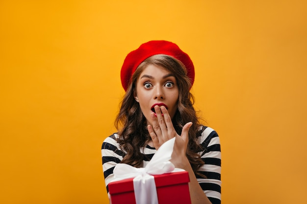 Niebieskooka kobieta wygląda na zszokowaną i pojawia się. zaskoczona dziewczyna z kręconymi włosami w czerwonym berecie i koszuli w paski trzyma pudełko.