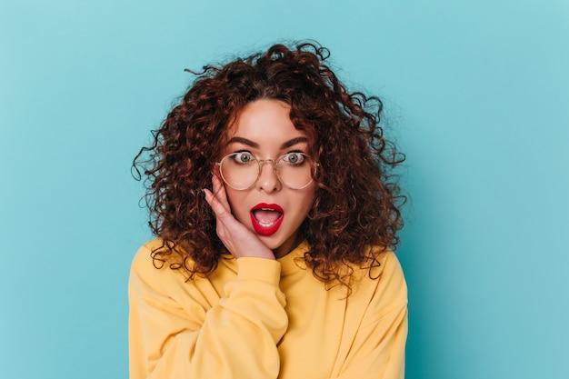Niebieskooka kobieta z czerwonymi ustami patrzy na aparat z otwartymi ustami ze zdziwienia. kręcone dziewczyna w żółtym swetrze pozowanie na niebieskiej przestrzeni.