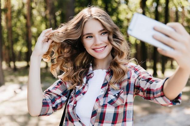Niebieskooka nieśmiała dziewczyna przy użyciu telefonu do selfie w parku lato. plenerowy portret eleganckiej blondynki pani bawi się włosami.
