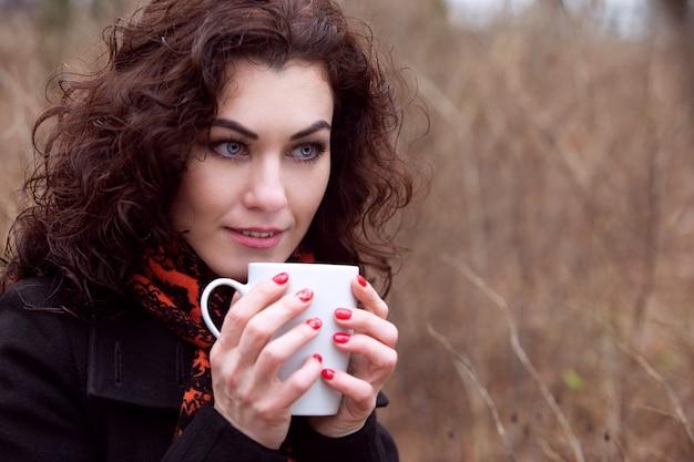Niebieskooka urocza dziewczyna w płaszczu i jasnym płaszczu przeciwdeszczowym w chłodne dni pije kawę w parku
