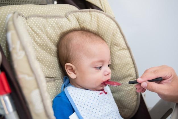 Niebieskooki chłopiec jedzenie - w wózek