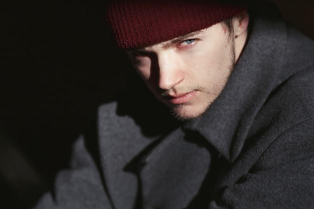 Niebieskooki mężczyzna w czerwonym kapeluszu pozuje w szarym płaszczu