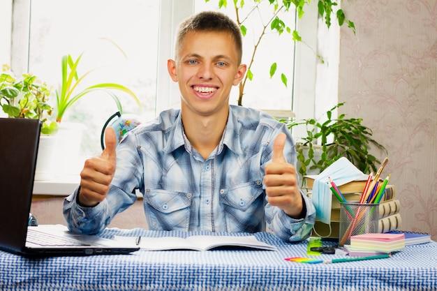 Niebieskooki młody mężczyzna ubrany w kraciastą koszulę siedzi przy biurku i wskazuje kciukiem w stronę klasy. koncepcja edukacji.