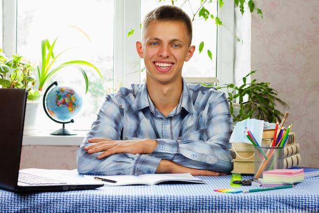 Niebieskooki młody mężczyzna ubrany w kraciastą koszulę siedzi w miejscu pracy i uśmiecha się. pandemia. koncepcja edukacji.