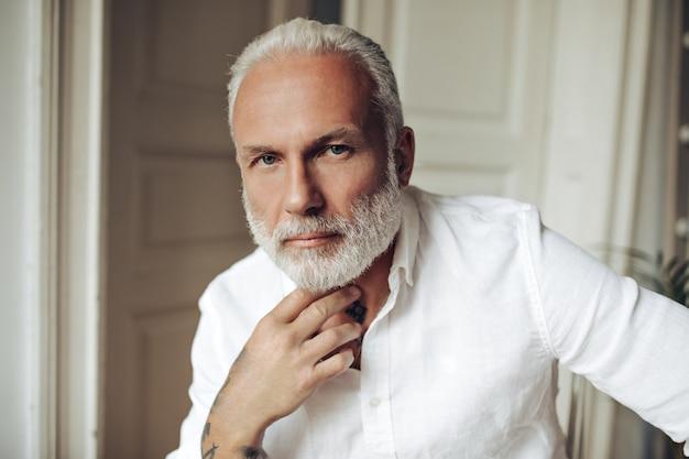 Niebieskooki przystojny mężczyzna w białej koszuli wygląda z przodu