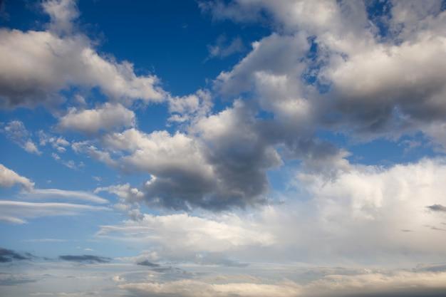 Niebo i chmury wieczorem w lecie. zachodzące słońce podkreśla chmury poniżej.