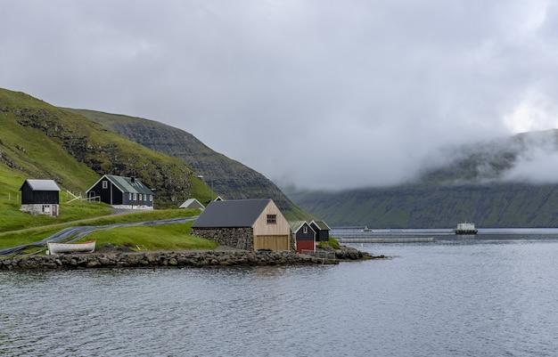 Niebo i domy na brzegu na wyspach owczych