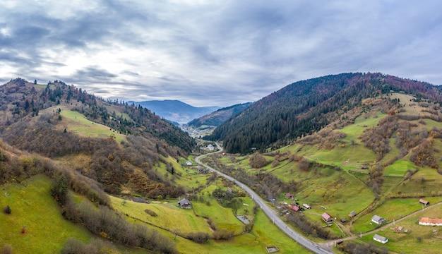 Niebo z białą i puszystą warstwą chmur nad zielonymi jesiennymi wzgórzami, panoramiczny strzał z lotu ptaka