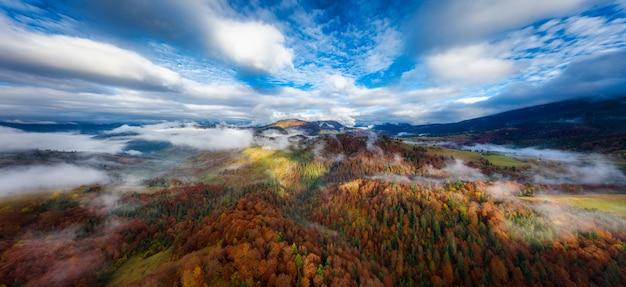 Niebo z białą i puszystą warstwą chmur nad zielonymi jesiennymi wzgórzami,