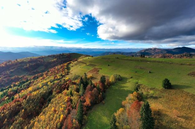 Niebo z białą i puszystą warstwą chmur nad zielonymi jesiennymi wzgórzami