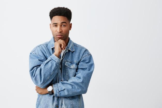 Niech pomyślę na białym tle portret młodego atrakcyjnego mężczyznę o jasnej karnacji z fryzurą afro w dżinsowej kurtce trzymającej podbródek ręką, patrząc w kamerę z zamyślonym wyrazem twarzy. skopiuj miejsce