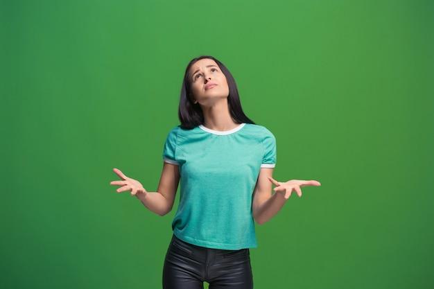 Niech pomyślę. pojęcie wątpliwości. wątpliwa zamyślona kobieta z zamyślonym wyrazem twarzy dokonująca wyboru. młoda kobieta emocjonalna. ludzkie emocje, koncepcja wyrazu twarzy. z przodu . studio. pojedynczo na modnej zieleni