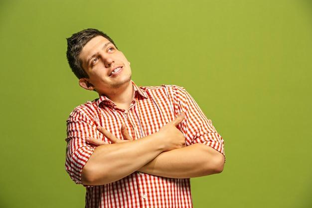 Niech pomyślę. pojęcie wątpliwości. wątpliwy, zamyślony człowiek z zamyślonym wyrazem twarzy dokonujący wyboru. młody człowiek emocjonalny. z przodu . studio. pojedynczo na modnej zieleni