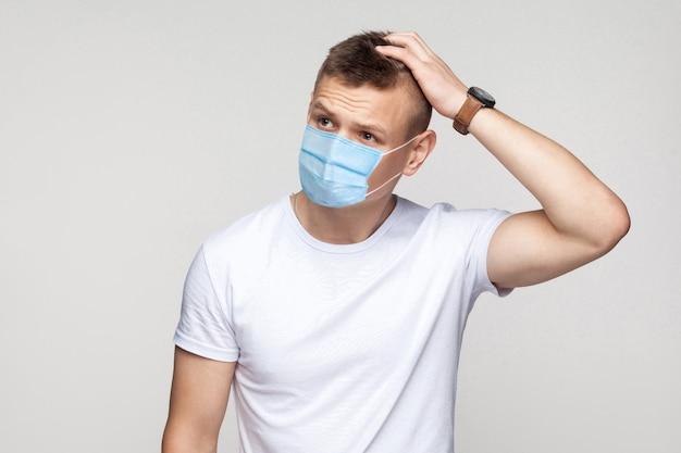 Niech pomyślę. portret rozważny młody człowiek w białej koszuli z chirurgiczną maską medyczną stoi, drapiąc się po głowie i myśląc, co robić. kryty strzał studio, na białym tle na szarym tle.