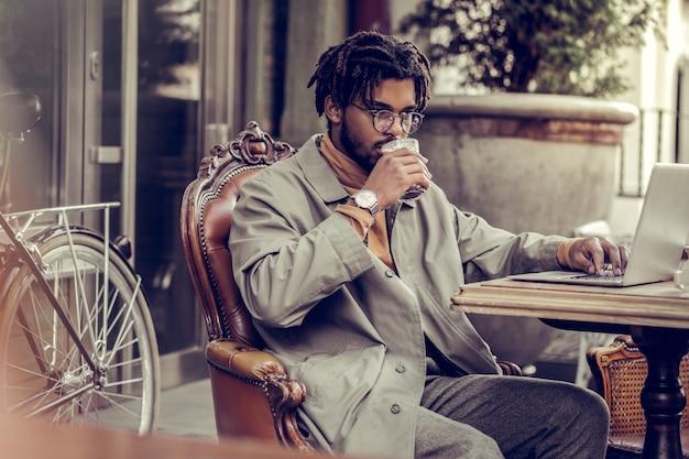 Niech pomyślę. skoncentrowany brunetka mężczyzna siedzi w miejscu pracy podczas picia kakao
