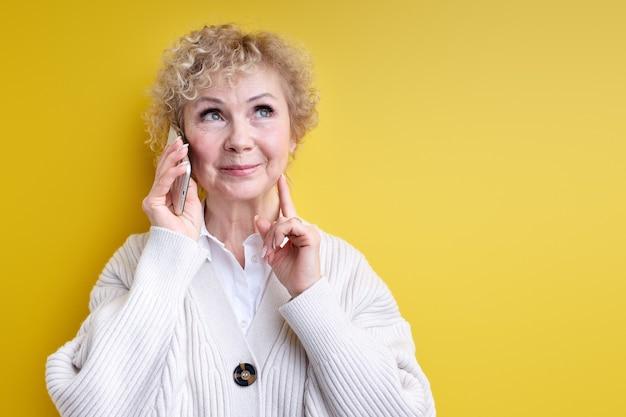 Niech pomyślę. starsza kobieta rozmawiająca przez telefon, skoncentrowana na myślach i słuchająca rozmowy, starsza pani z kręconymi siwymi włosami, wyglądająca przyjaźnie i optymistycznie, patrząc w górę