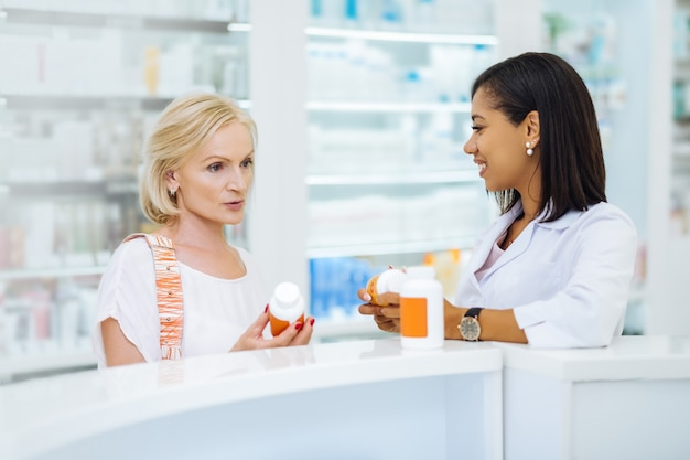 Niech pomyślę. wesoła brunetka aptekarz opiera się o stół podczas demonstrowania medycyny