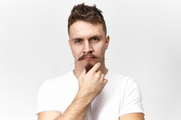 Niech pomyślę. zamyślony, zamyślony młody mężczyzna rasy kaukaskiej ze stylowym wąsem, dotykający brody koziej bródki, zamyślony i głęboko zamyślony. mowa ciała i ludzka mimika