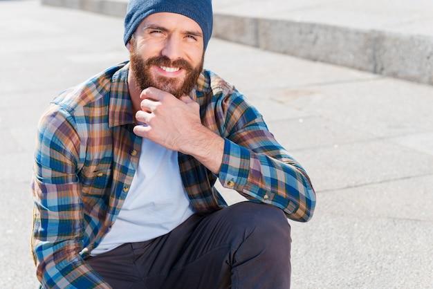 Niech to będzie zwyczajne. przystojny młody brodaty mężczyzna trzyma rękę na brodzie, siedząc na zewnątrz