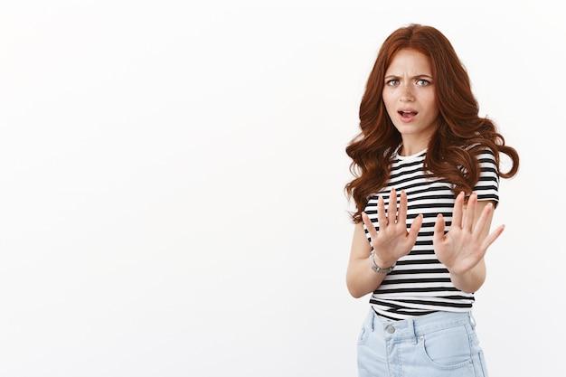 Niechętna, zniesmaczona ruda dziewczyna nie zgadza się, odrzuca ofertę, wyciąga ręce w znak stop, cofa się zaniepokojona i rozczarowana, wyraża niechęć i niechęć, odrzuca propozycję