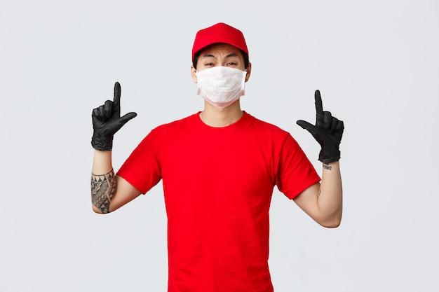Niechętnie lub przestraszony, niepewny azjatycki jęczący facet, krzywiący się, wskazując palcami w górę, noś mundur dostawczy, czerwoną czapkę i koszulkę, firma chroń zdrowie personelu za pomocą masek ochronnych i rękawic