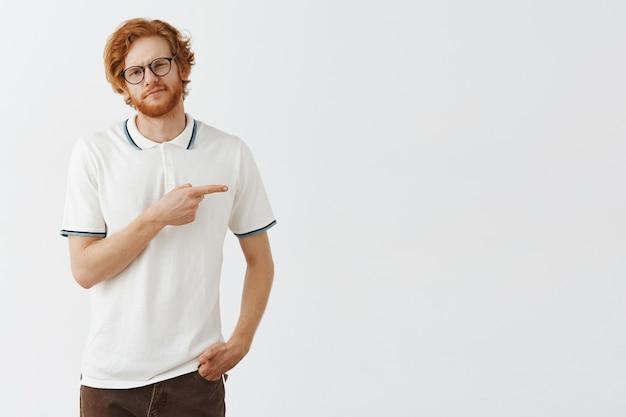 Niechętny i smutny brodaty rudy facet pozuje w okularach na białej ścianie