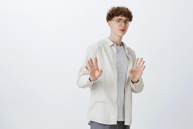 Niechętny nastoletni facet pozuje na białej ścianie